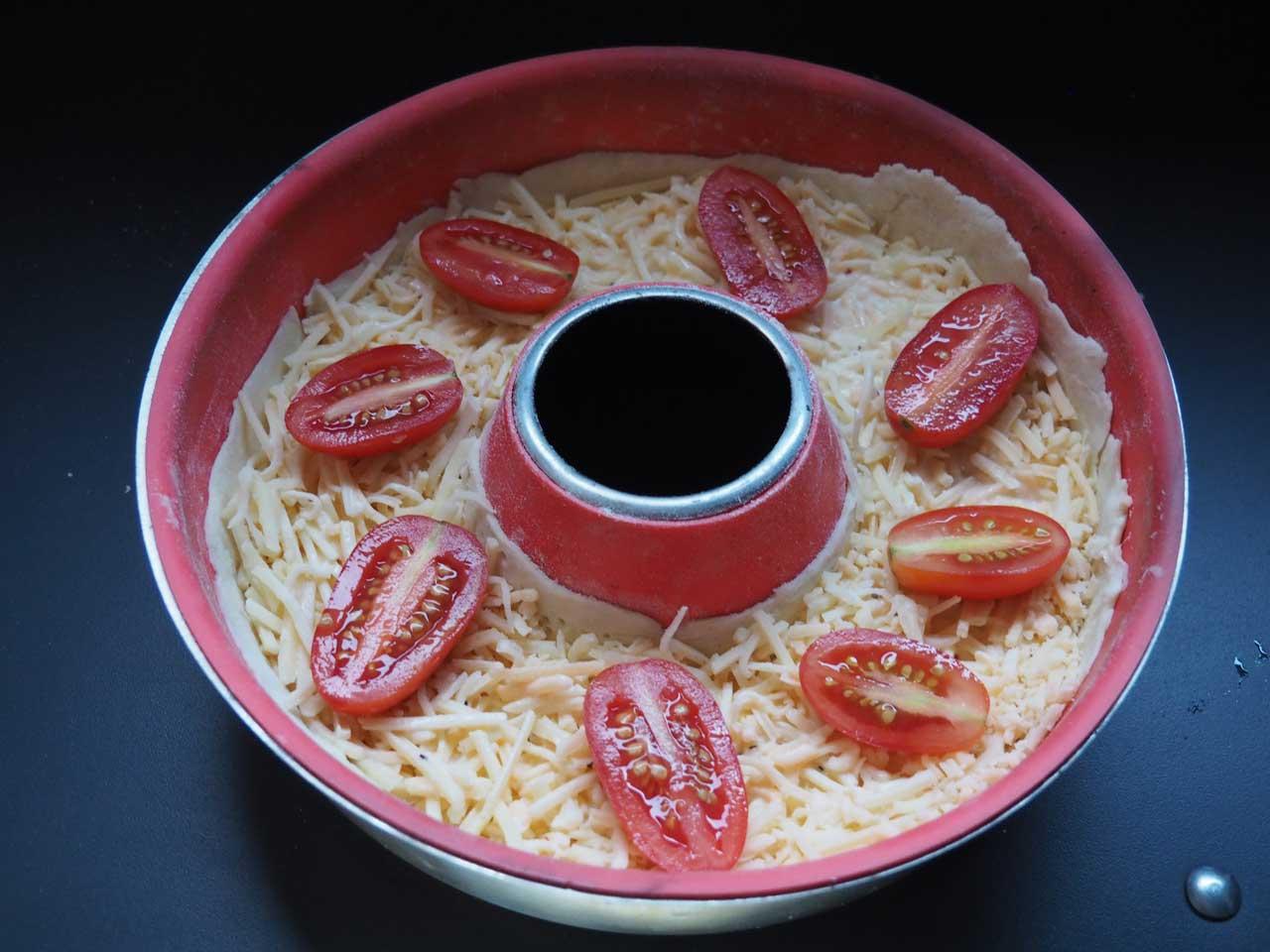 Die Käsemischung mit dem Guss übergiessen und am Schluss die Cherrytomaten darauf verteilen