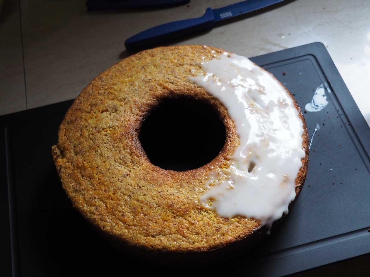 Zuckerguss gleichmässig auf dem warmen Kuchen verstreichen