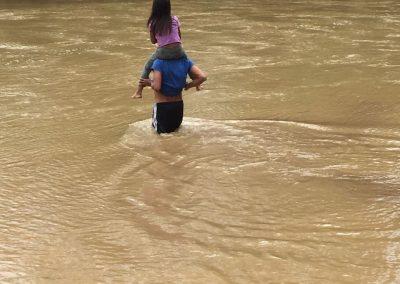 Ein Vater trägt seine Tochter durch den Fluss.